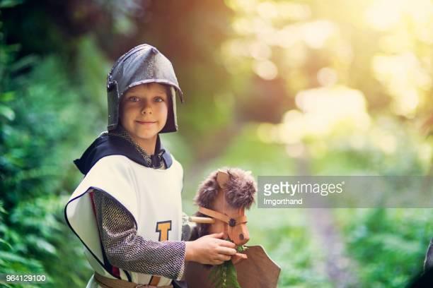 Niedliche kleine Ritter Fütterung sein Pferd im Wald