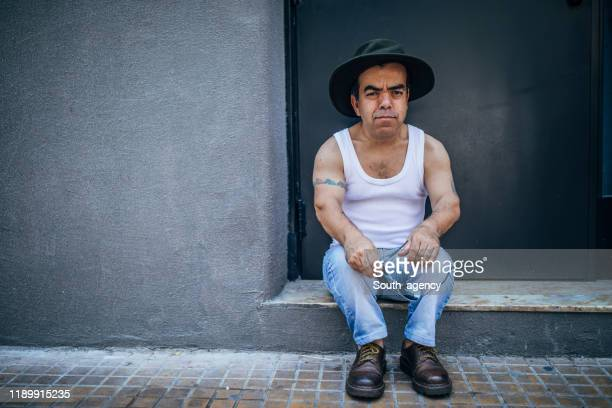 cute little man sitting on the sidewalk - dwarf man stock pictures, royalty-free photos & images