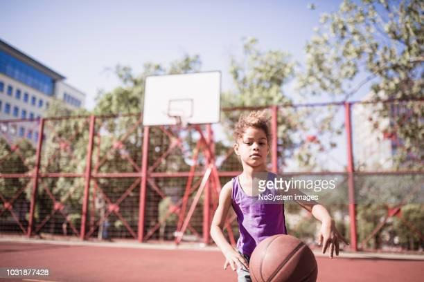 bonitinho misturado menina corrida jogando basquete ao ar livre - miscigenado - fotografias e filmes do acervo