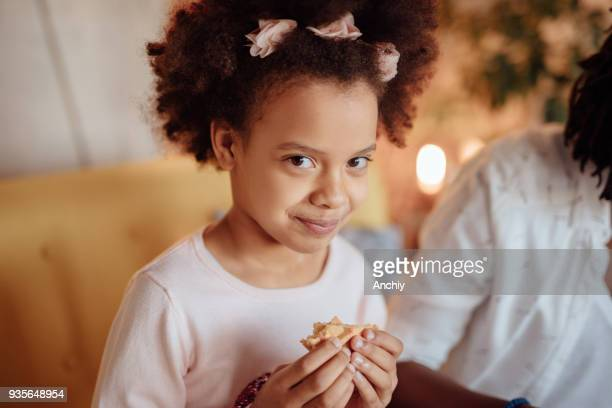Cute little preschool girl looking at camera and eating waffles