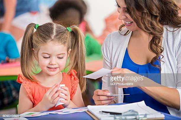 Cute little preschool girl working on flashcards with teacher