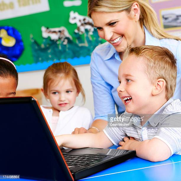 Cute little preschoolers learning to use computer