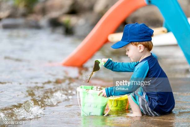 cute little redhead boy playing with sand on beach - lake auburn stock photos and pictures