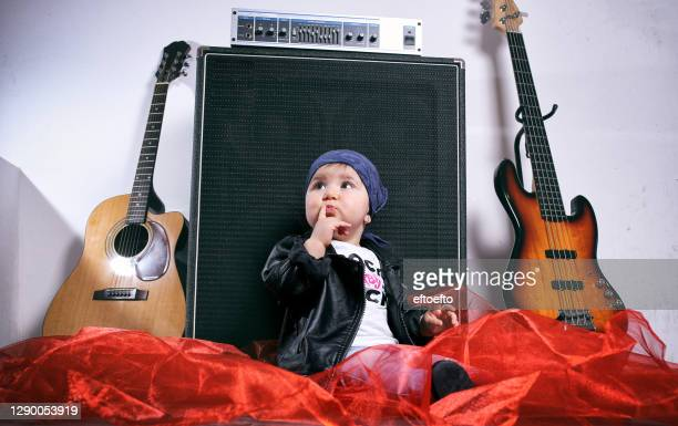 cute little rocker-baby girl seating by two  guitars - member of congress stock pictures, royalty-free photos & images