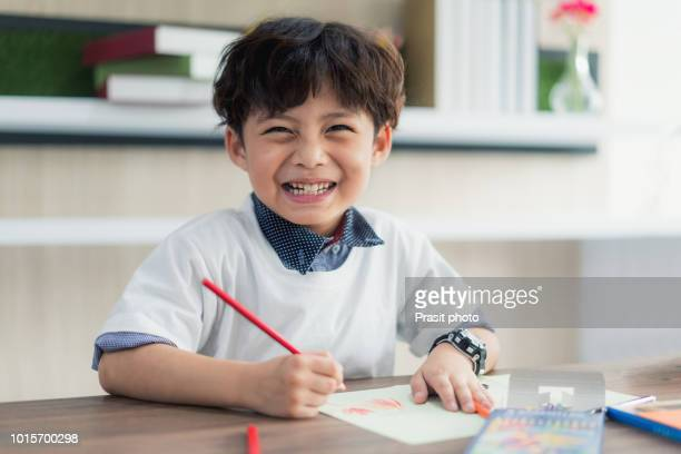 cute little school boy drawing with color pencilsand looking at camera at classroom in school. - 6 7 jahre stock-fotos und bilder