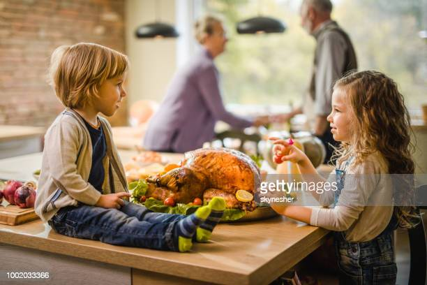 cute little siblings talking on thanksgiving day at their grandparents'. - kids thanksgiving stock pictures, royalty-free photos & images