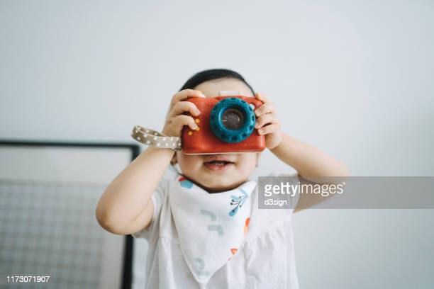 cute little toddler girl having fun and taking photos with toy camera at home - toy stock pictures, royalty-free photos & images