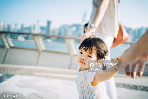 cute little toddler girl holding her mother and father's hand strolling along the promenade against urban cityscape on a lovely sunny day - prosperity stockfoto's en -beelden