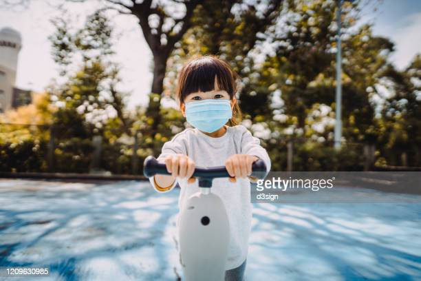 cute little toddler girl riding a scooter joyfully in the park. she is wearing a surgical mask to prevent the spread of cold and flu and viruses - safety stock pictures, royalty-free photos & images