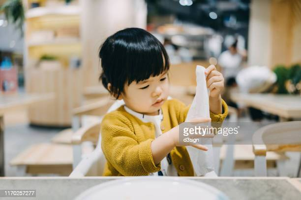cute little toddler girl wiping hands and mouth by herself after meal in a restaurant - ティッシュ ストックフォトと画像