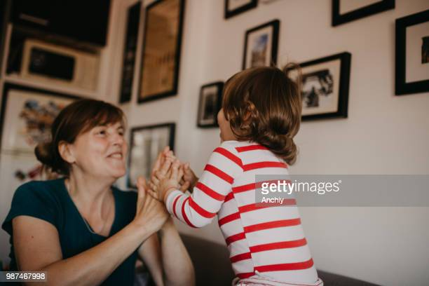 Cute little toddler playing with grandmother