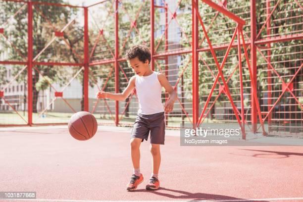 niedliche kleine mixed rennen junge, basketball spielen - sporting term stock-fotos und bilder