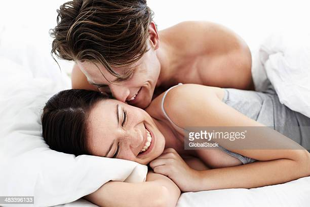Cute loving couple smiling in bed