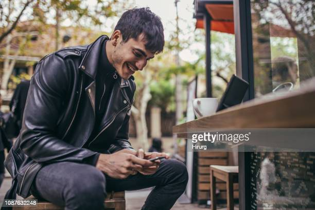 cute man texting and smiling - leather jacket stock pictures, royalty-free photos & images