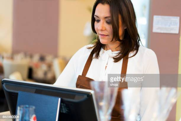 Cute middle aged waitress in a coffee shop standing by the cash register