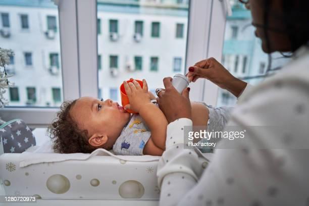 süße gemischte rasse baby junge beißen sein spielzeug, während seine mutter eine hautlotion auf seinen bauch auftragen - neurodermitis stock-fotos und bilder