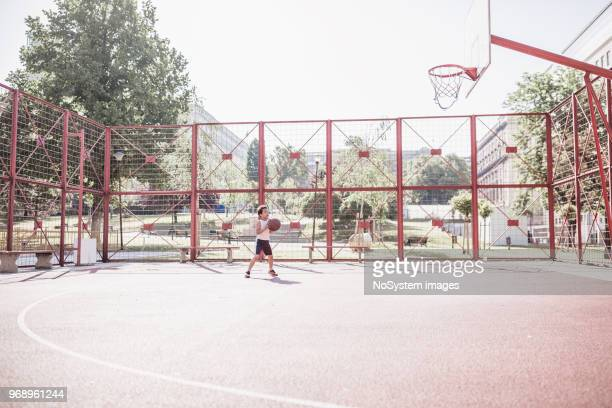 Chico lindo de raza mixta jugando baloncesto al aire libre en la cancha de baloncesto