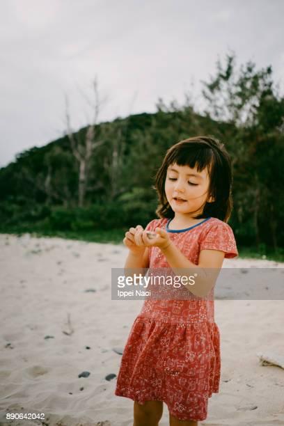 Cute mixed race girl holding seashells, Okinawa, Japan