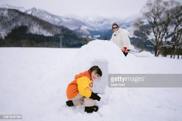 Cute mixed race girl smiling at camera while making igloo on snowy field in mountains