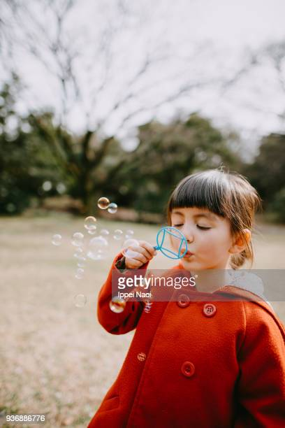 Cute mixed race little girl blowing bubbles in park