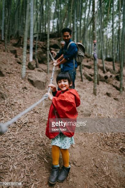 Cute mixed race little girl hiking in bamboo grove