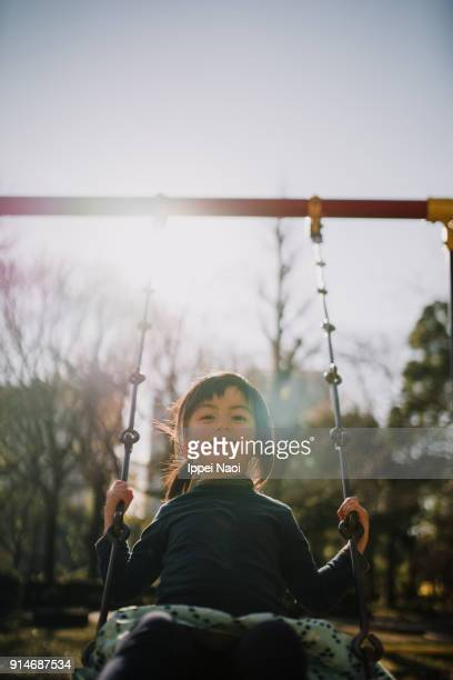 Cute mixed race little girl playing on swing, Tokyo