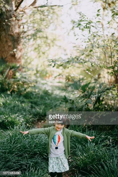 cute mixed race little girl walking through forest with arms outstretched, tokyo - superman stock pictures, royalty-free photos & images