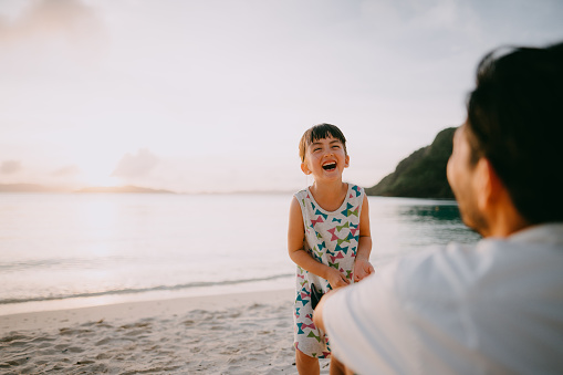 Cute mixed race preschool girl laughing on beach at sunset, Okinawa, Japan - gettyimageskorea