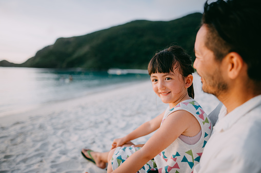Cute mixed race preschool girl sitting on father's lap on beach at sunset, Okinawa, Japan - gettyimageskorea