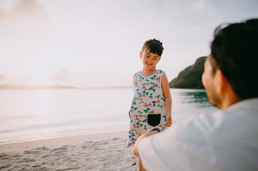 Cute mixed race preschool girl smiling on beach at sunset, Okinawa, Japan - gettyimageskorea