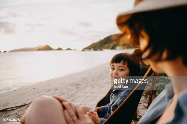 cute mixed race toddler girl with mother on beach, okinawa, japan - outdoor pursuit stock pictures, royalty-free photos & images
