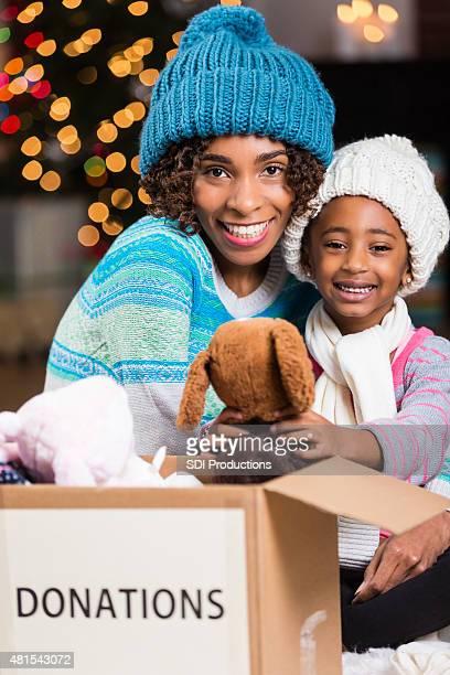 Süße Mutter und Tochter Sortierung Kisten von Weihnachten spenden