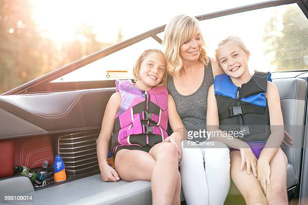 Cute mother and daughters sitting in a boat
