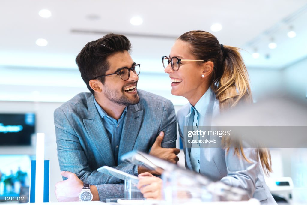 Cute multicultural couple in formal wear smiling and looking for new tablet to buy. Tech store interior. : Stock Photo