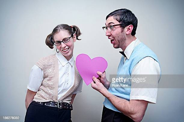 Cute Nerd Guy and Girl in Love Holding A Heart