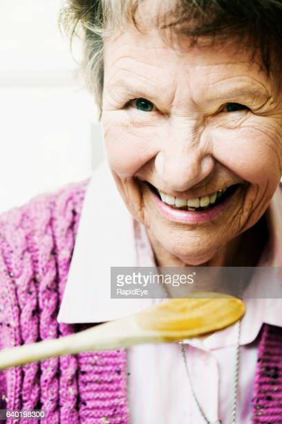 Cute old lady smiles as she lifts wooden tasting spoon