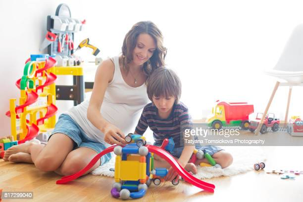 Cute pregnant mother and child boy playing together indoors at home with toys