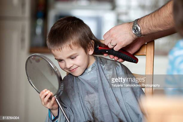 Cute preschool boy, having haircut at home, given by his father, holding mirror
