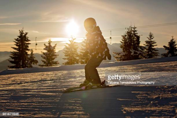 Cute preschool child, boy, skiing on sunset in austrian Alps, scenery landscape