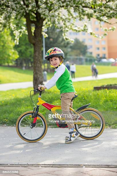 Cute preschool children, riding bikes in the park, springtime