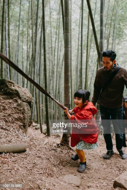 Cute preschool girl climbing mountain with bamboo grove