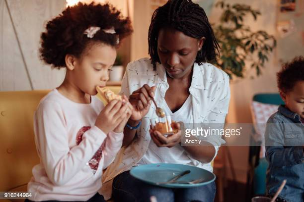 cute preschool girl eating breakfast with her mom and sister - interracial cartoon stock photos and pictures
