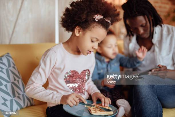 cute preschool girl eating waffle while mom and her sister playing on tablet - interracial cartoon stock photos and pictures