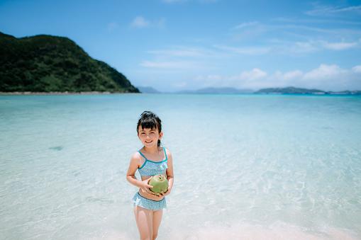 Cute preschool girl holding coconut on tropical beach, Okinawa, Japan - gettyimageskorea