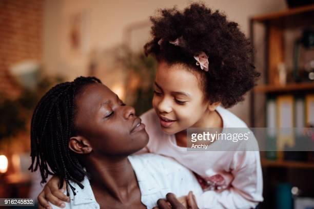 彼女の母親を抱いてかわいい幼稚園女の子 - interracial cartoon ストックフォトと画像