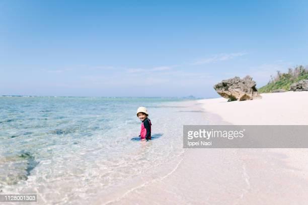 Cute preschool girl on white sand tropical beach, Okinawa, Japan