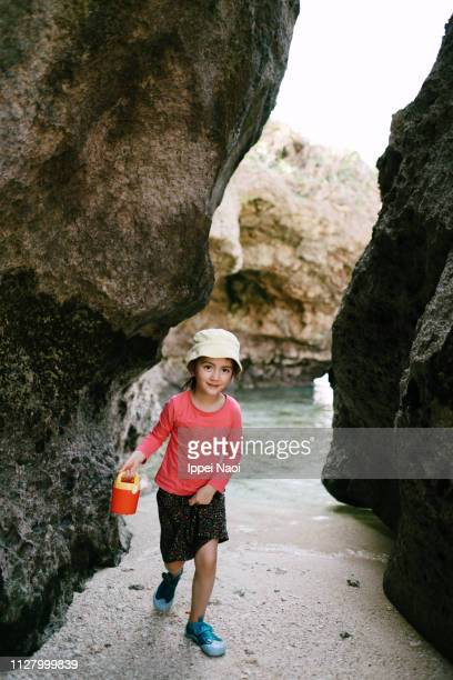 Cute preschool girl playing on beach in cave, Okinawa, Japan