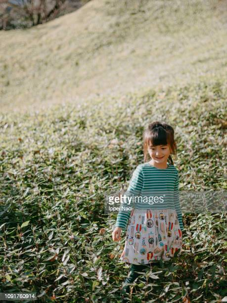 Cute preschool girl smiling and walking on the grassy hill