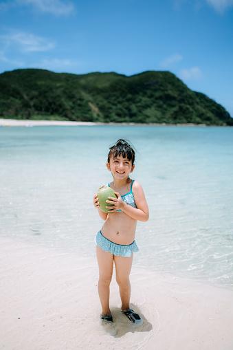 Cute preschool girl with coconut on tropical beach, Okinawa, Japan - gettyimageskorea