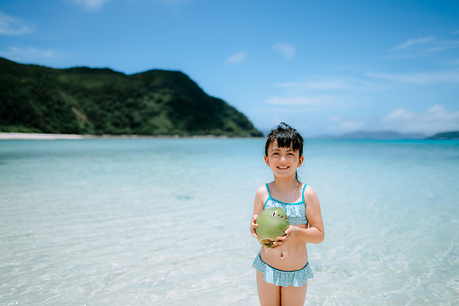 Cute preschool girl with coconut smiling at camera on tropical beach, Okinawa, Japan - gettyimageskorea